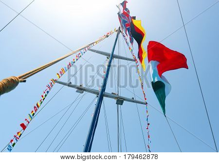 Flags of different countries on the mast of sailboat