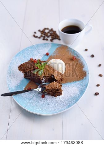 Chocolate brownie with ice cream on a blue plate next to a cup of coffee. Chocolate cake with coffee