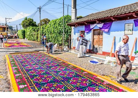 Antigua, Guatemala - March 26 2017: Locals make dyed sawdust procession carpets during Lent against backdrop of Agua volcano in colonial town with most famous Holy Week celebrations in Latin America.