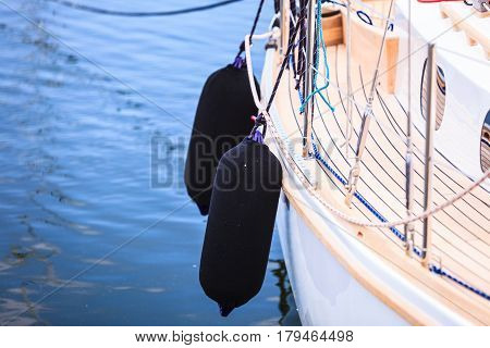Side Of Hull Sailboat With Black Fenders