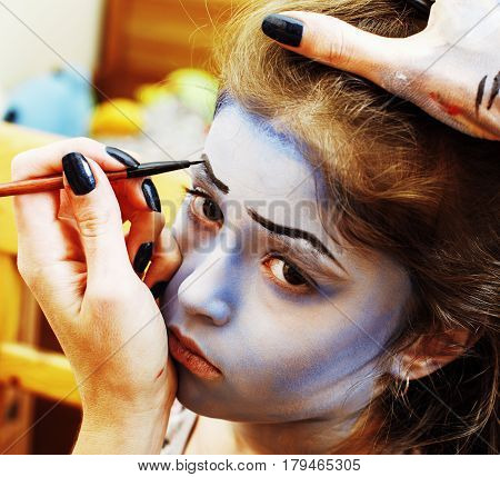 little cute child making facepaint on birthday party, zombie Apocalypse facepainting, halloween preparing concept, lifestyle people close up