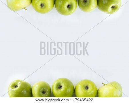 Horizontal seamless background with green apples. Fresh apples on a white background. Apples at border of image with copy space for text.