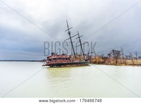 Rusty leaning shipwreck marooned near shore on lake under a stormy blue sky