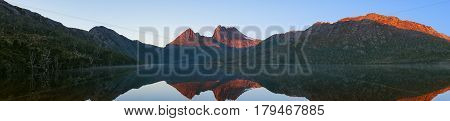 Picturesque Panorama Of Mountain Range Reflected In Lake On Sunrise