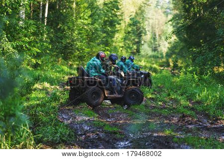 Summer Activities for adults - a trip on quad bikes on the dirty road. Man on ATV unfold on the track in the mud for the continuation of cross-country race.