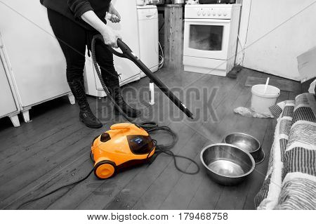 Woman cleaning floor with steam or hot water spray kitchen interior. Selective color shot