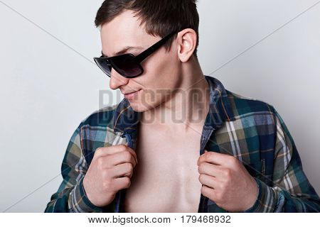 A handsome guy with unbuttoned shirt and sunglasses posing over white background showing his beautiful body. Presss muscles of sports guy. The concept of bodybuilding and healthy lifestyle.