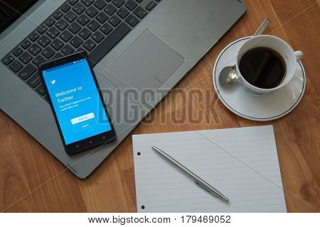 Nitra, Slovakia, march 28, 2017: Twitter application in a mobile phone screen. Workplace with a laptop, an earphones, notepad, pen and coffee on wooden background