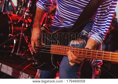Bass guitar player on stage during a performance in yarih lights close up. Guitarist during the concert. Soft focus.