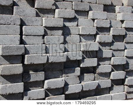 Uneven Stack of Grey Concrete Road Bricks Perspective Background