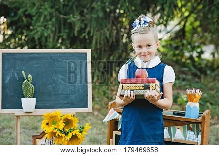 Portrait Of A Beautiful Young First-grader Standing With Books