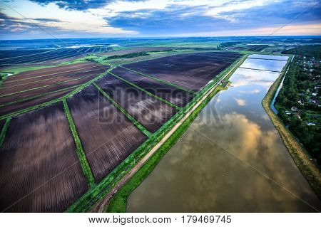 Village from the bird's-eye view at sunrise, cultivated land and lake with duckweed