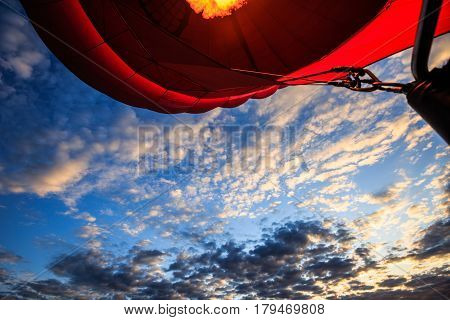 Fire inside a red air balloon heart form rises up at dawn