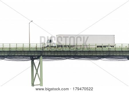 An eighteen-wheeler crosses a bridge with a blank white cloudy sky in the background perfect for your copy.