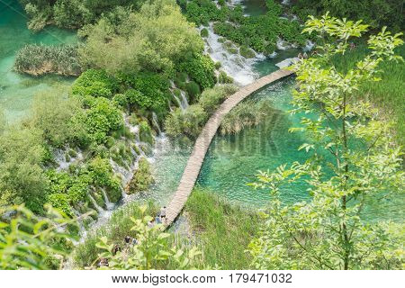 An aerial view of tourists entering a timber walkway across lakes and waterfalls at Plitvice National Park in Croatia.