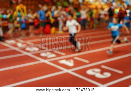 Blurred image of children athletes on a racetrack during finishing. Participants of the race finish in the race. The background image, an abstraction.