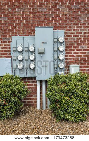 Vertical shot of a group of Electric Meters on a red brick wall for a Multi-family Apartment Building.