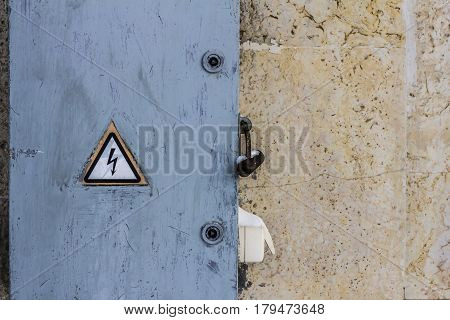 electrical hazard sign placed on a  locked electric power dashboard on a scratched painted wall