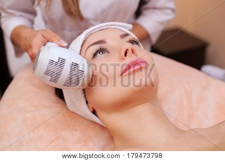 The Doctor-cosmetologist Makes The Procedure Cryotherapy Of The Facial Skin Of A Beautiful, Young Wo