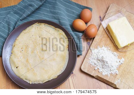 Top view of the ingredients for making traditional thin pancakes and finished pancakes on a plate. The process of making pancakes. Soft focus.