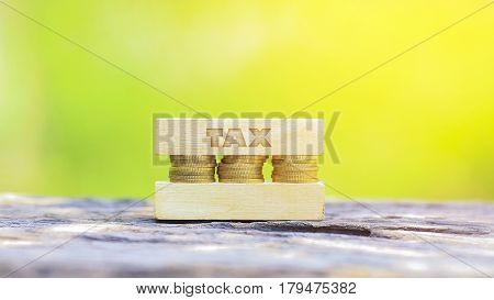 Business Concept - Tax Word, Golden Coin Stacked With Wooden Bar On Shallow Dof Green Background