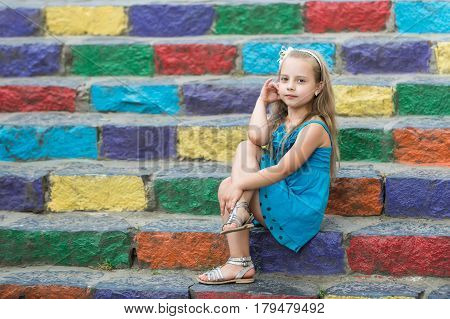 Small Baby Girl In Blue Dress On Colorful Stairs