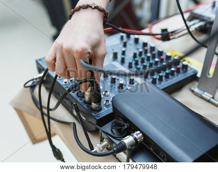 DJ connects the sound equipment for the event or party. man's hand holding the audio connector on the background of the sound equipment.