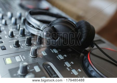DJ Mixer with headphones. Elements and details of artists working tools - DJ console with knobs and black headphones. Soft focus.