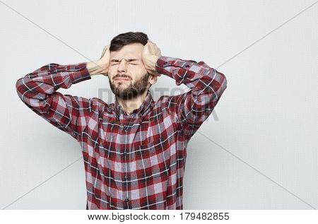 Studio shot of young sad and depressed man in shirt. He is looking desperate in pain suffering migraine and headacheclosing eyes. Isolated on white background. Negative Emotions concept.