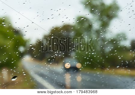 Rain Drops On Car Windshield And Blurred Car On Wet Road