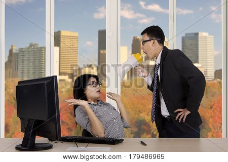 Image of young boss looks angry while reprimanding his employee with a megaphone while standing near the window