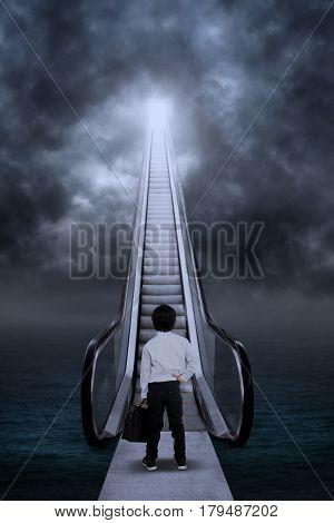 Business kid at the escalator under dark clouds outdoor