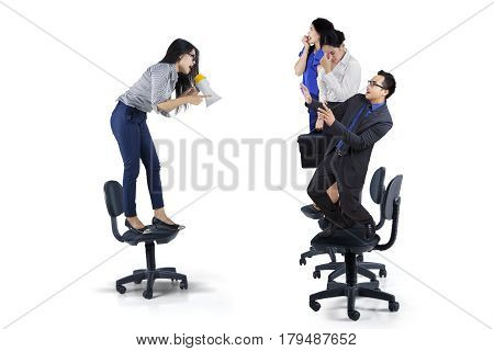 Picture of young businesswoman yelling to her teamwork with a megaphone isolated on white background