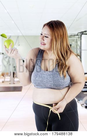 Overweight young woman with blonde hair holding a green apple fruit while measuring her belly with measure tape in fitness center