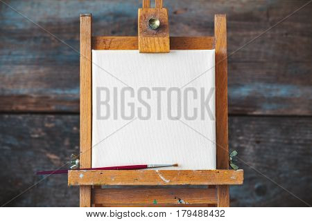 Empty canvas on easel on old wooden background.