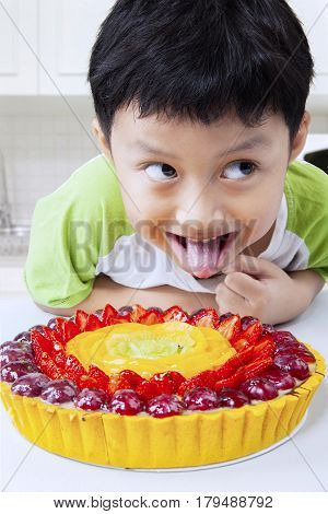 Photo of a little boy looks hungry with a strawberry pie in the kitchen at home