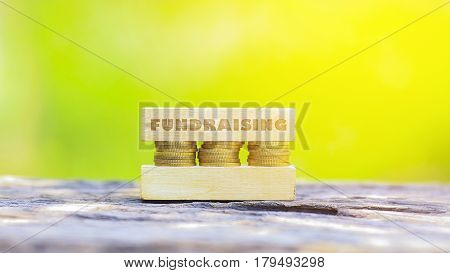 Business Concept -fundraising Word, Golden Coin Stacked With Wooden Bar On Shallow Dof Green Backgro