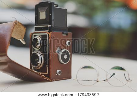 Classic oldschool vintage camera and glasses on the table