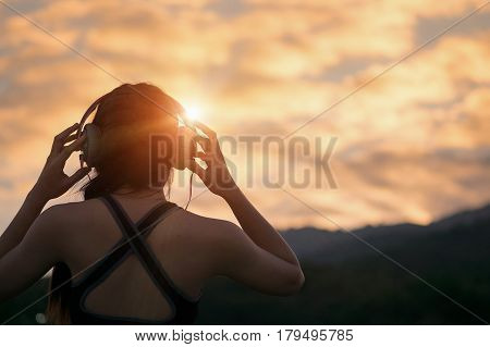 young fitness woman waering headphones at sunrise moutain. relax and healthy conecpt.