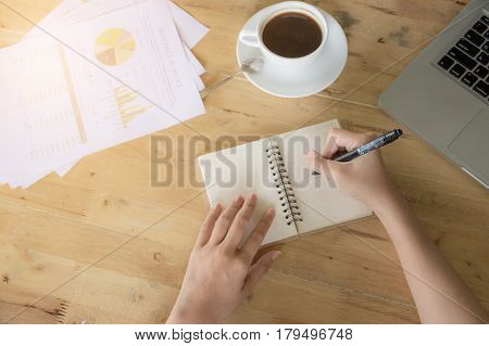 Business Women Writting On Notebook And Hot Coffee And Turnover Document Papaer Sheets On Wooden Tab