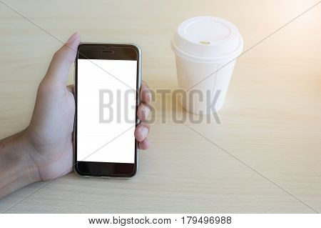 Close up of a man holding and using smartphone with blank mobile and cup of coffee .Smart phone with blank screen and can be add your texts or others on smart phone.