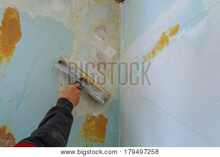 The process of putty the walls with a large spatula wall putty to defective poster