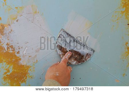 Closeup of a man aligning a wall with spatula and trowel. wall putty