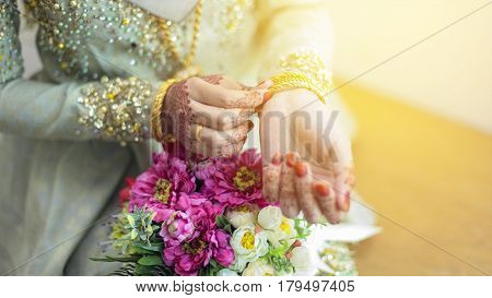 graceful poses of girls hand wearing gold bangles with beatiful flower selective focus shallow DOF