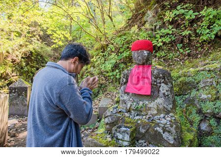 NIKKO, JAPAN - OCTOBER 15 ,2016 : Nikko, Japan Jizo statues in Kanmangafuchi Abyss and Tourists worship the Buddha.