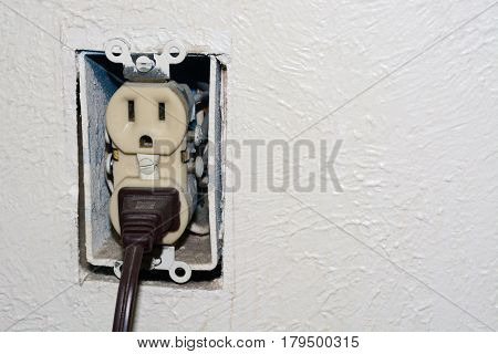 Home danger of electrical outlet without cover plate with electrical plug plugged into socket