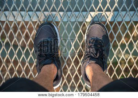 Feet with shoes on metal bridge floor top view