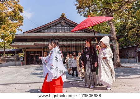 TOKYO JAPAN - APRIL 19 2014: Japanese wedding ceremony at Shrine on April 192014. As Meiji Jingu Shrine It's possible to see wedding parties parading through the inner ground of the shrine