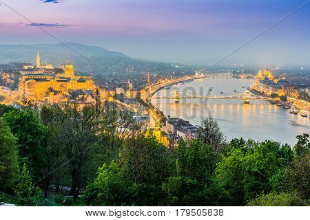 BUDAPEST HUNGARY - APRIL 13 2016: View of Budapest from Gellert Hil with Buda Castle Danube with Szechenyi Bridge and Margaret Bridge Hungarian Parliament Building and St. Stephen's Basilica.