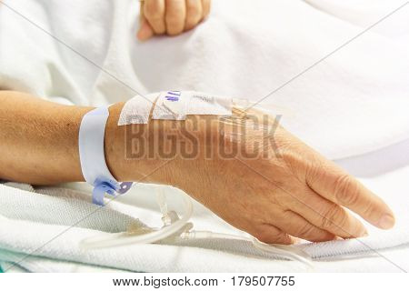 Closeup saline water line at the hand of patient on bed in hospital room infusion line in a patients hand